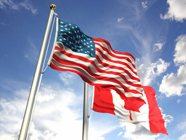American and Canada flags waving against the sky stock photo