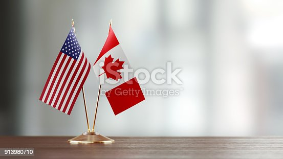 istock American And Canadian Flag Pair On A Desk Over Defocused Background 913980710