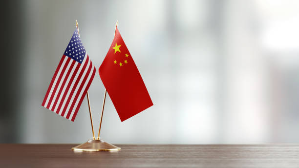 american and chinese flag pair on a desk over defocused background - cinese foto e immagini stock