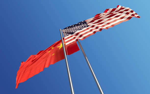 American and Chinese Flags Waving With Wind: Dispute Concept American and Chinese flags are waving with wind at opposite directions on a blue sky. Low angle view. Dispute and conflict concept. Horizontal composition with copy space. Great use for China and United States of America related concepts. diplomacy stock pictures, royalty-free photos & images
