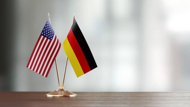 amerikanische und deutsche flagge paar auf einem schreibtisch über defokussierten hintergrund - deutschland usa stock-fotos und bilder