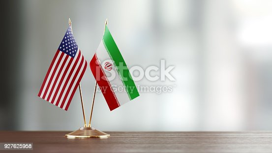 istock American And Iranian Flag Pair On A Desk Over Defocused Background 927625958