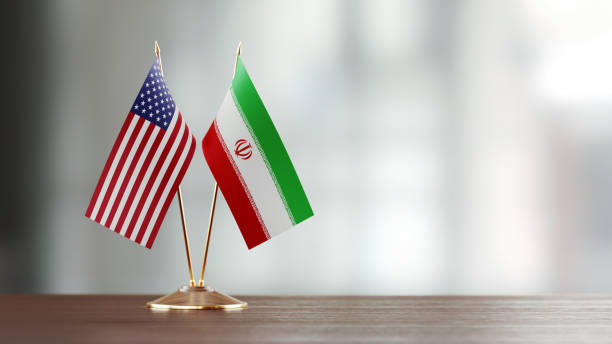 American And Iranian Flag Pair On A Desk Over Defocused Background American and Iranian flag pair on desk over defocused background. Horizontal composition with copy space and selective focus. iran stock pictures, royalty-free photos & images