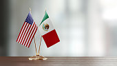 American and Mexican flag pair on desk over defocused background. Horizontal composition with copy space and selective focus.