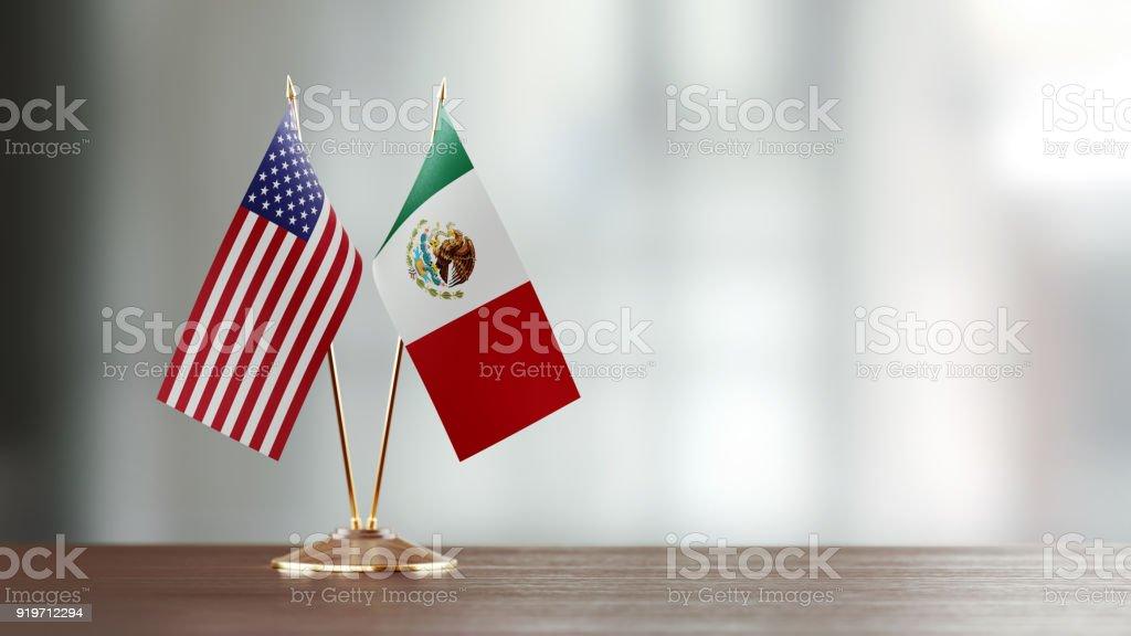 Par de la bandera de Estados Unidos y México en un escritorio sobre fondo Defocused - foto de stock
