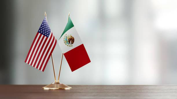 par de la bandera de estados unidos y méxico en un escritorio sobre fondo defocused - bandera mexico fotografías e imágenes de stock