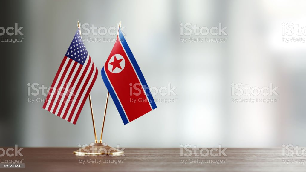 American And North Korean Flag Pair On A Desk Over Defocused Background stock photo