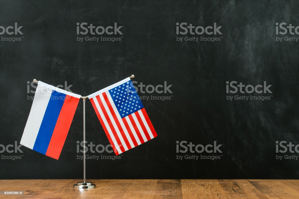 American and Russian flag on flagpole stock photo