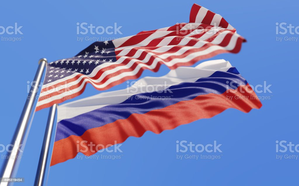 American And Russian Flags Waving With Wind On Blue Sky stock photo