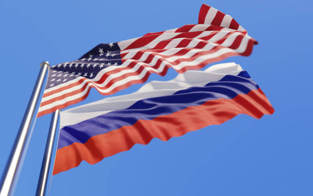 American And Russian Flags Waving With Wind On Blue Sky High quality 3d render of American and Russian flags waving with wind on a blue sky. Low angle view with copy space and selective focus. sanctions stock pictures, royalty-free photos & images