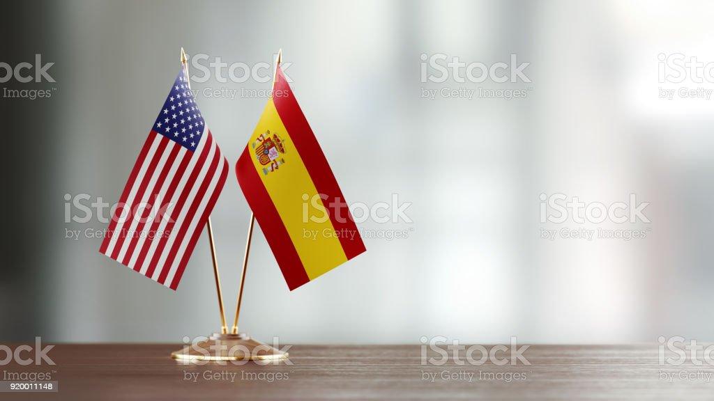 Par de bandeira americana e espanhola em uma mesa sobre fundo desfocado - foto de acervo