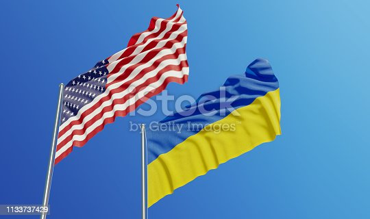 American and Ukrainian flags are waving with wind over  blue sky. Low angle view. Dispute and conflict concept. Horizontal composition with copy space.
