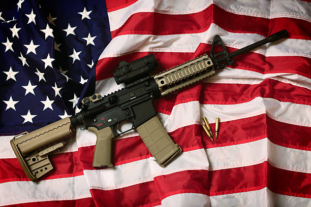 American AR-15 An AR-15 rifle with bullets on an American flag, a symbol of the right of patriotic Americans to bear arms, guaranteed by the Second Amendment. ar 15 stock pictures, royalty-free photos & images
