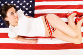 Photo of an attractive young woman striking a pose on an american flag.