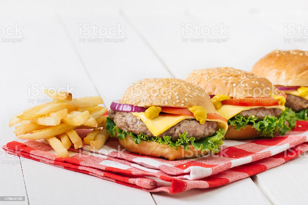 Close -up photo ,american mini beef burgers with cheese .