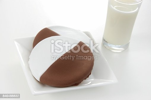 American traditional black and white or half moon cookies served with a glass of cold milk.