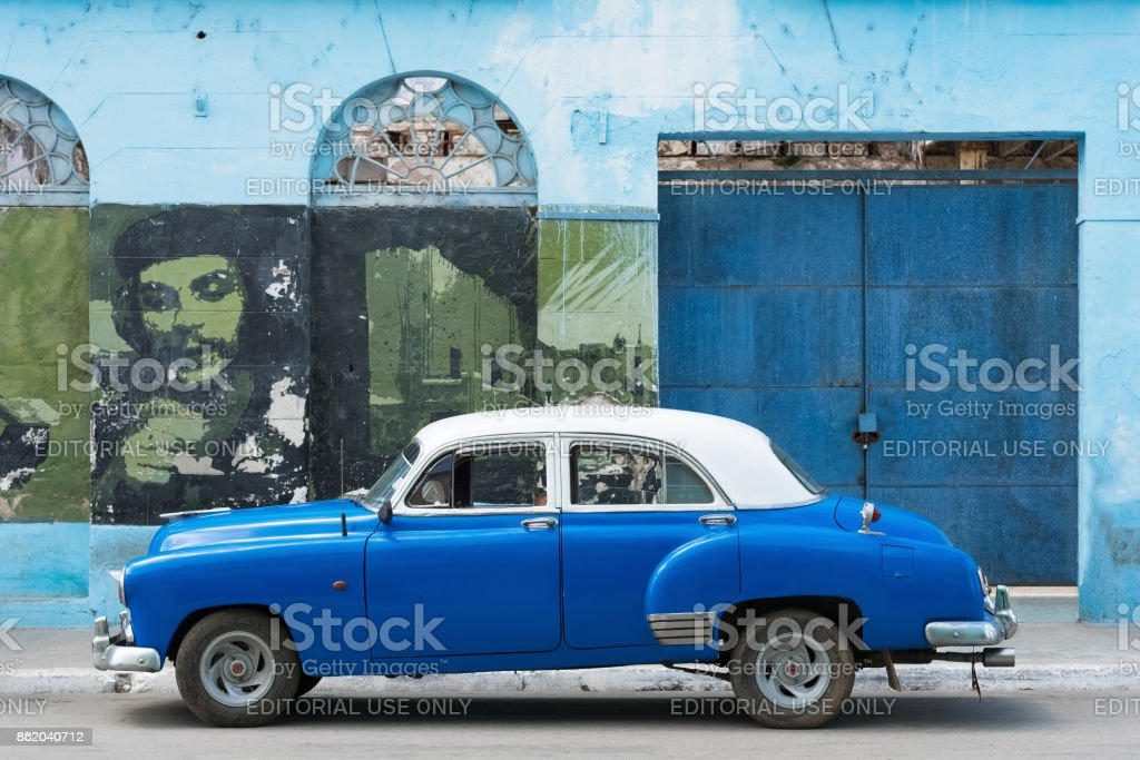 American blue Buick classic car parked before a house facade with revolution graffiti in Santa Clara Cuba - Serie Cuba Reportage stock photo