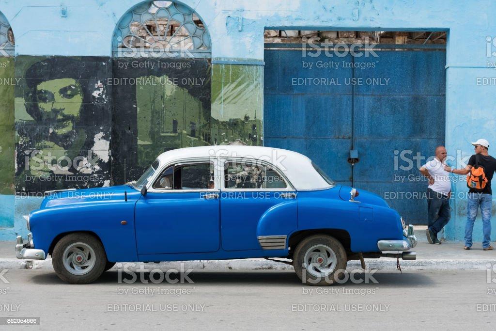American blue Buick classic car parked before a house facade with revolution graffiti in Santa Clara Cuba - Serie Cuba Reportage stock photo