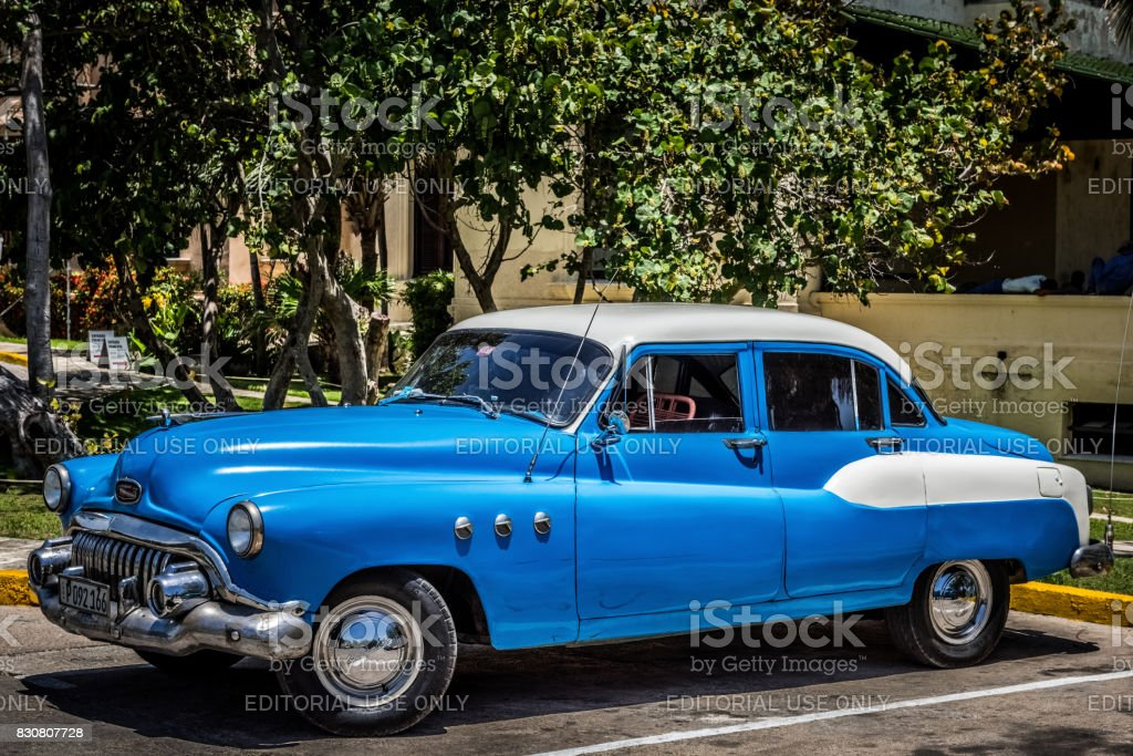 HDR - American blue Buick Eight classic car parked under palms on the beach in Varadero Cuba -Serie Cuba Reportage stock photo