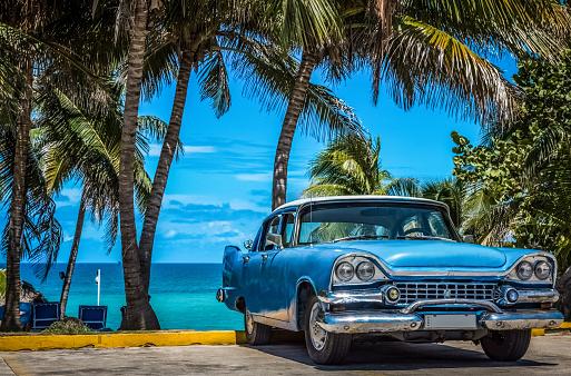 American blue vintage car parked under palms in Varadero Cuba