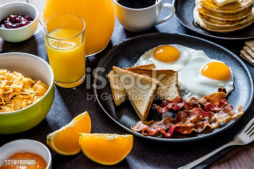 High angle view of an American breakfast made with fried eggs, toasted bread, bacon, pancakes, orange juice, coffee, and oranges.