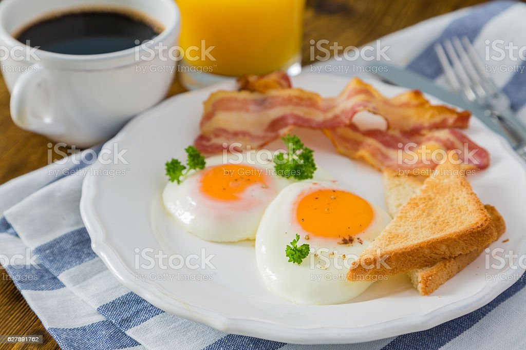 American breakfast with sunny side up eggs, bacon, toast, pancakes stock photo