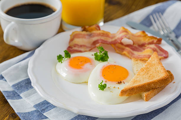 american breakfast with sunny side up eggs, bacon, toast, pancakes - 朝食 ストックフォトと画像