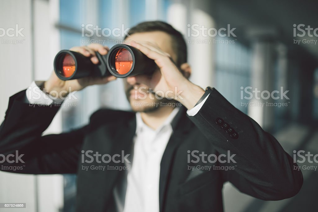 american businessman using binoculars in office stock photo