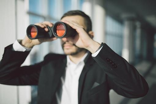 American Businessman Using Binoculars In Office Foto de stock y más banco de imágenes de Adulto