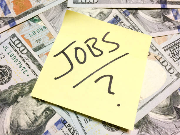 american cash money and yellow paper note with text jobs with question mark - unemployment стоковые фото и изображения