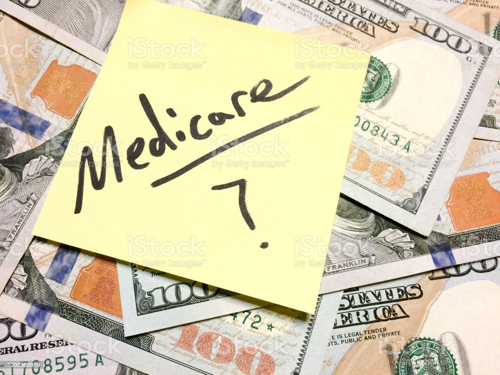American cash money and yellow sticky note with text Medicare with...