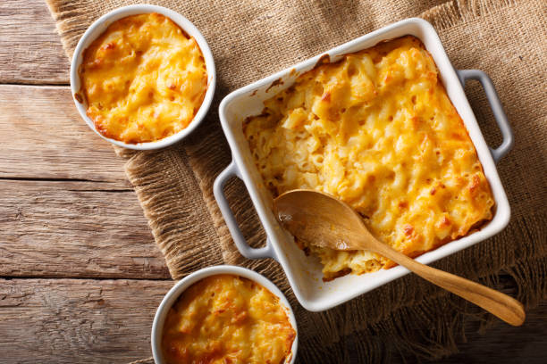 American casserole macaroni and cheese in baking dish close up. Horizontal top view American casserole macaroni and cheese in baking dish close up on the table. Horizontal top view from above macaroni stock pictures, royalty-free photos & images