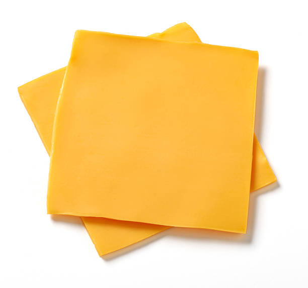 American Cheese Slices Two slices of processed American cheese on white background with natural shadow. burwellphotography stock pictures, royalty-free photos & images