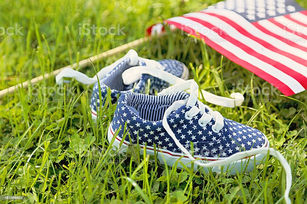 American children's sneakers and United States of America flag. stock photo