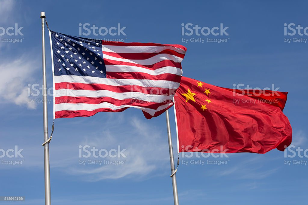 American Chinese windy day flags fly together on flagpole stock photo