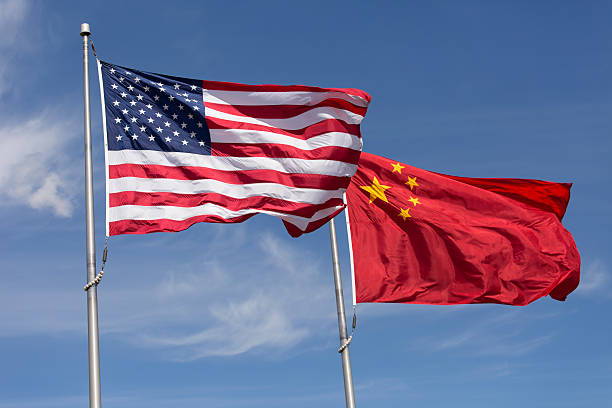 american chinese windy day flags fly together on flagpole - usa stock pictures, royalty-free photos & images