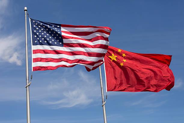 americano cinese giornata ventosa bandiere volare insieme sul pennone - cina foto e immagini stock