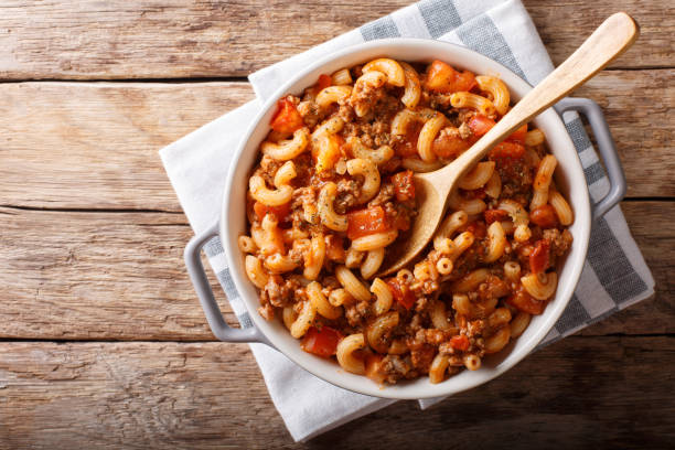 american chop suey, american goulash, with elbow pasta, beef and tomatoes close-up. Horizontal top view stock photo
