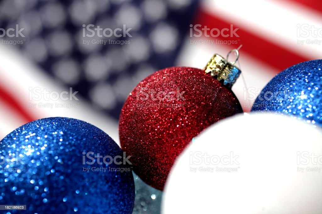 American Christmas XXXL photo of red, white and blue Christmas ornaments in front of an American flag.  Selective focus on center ornament. American Culture Stock Photo