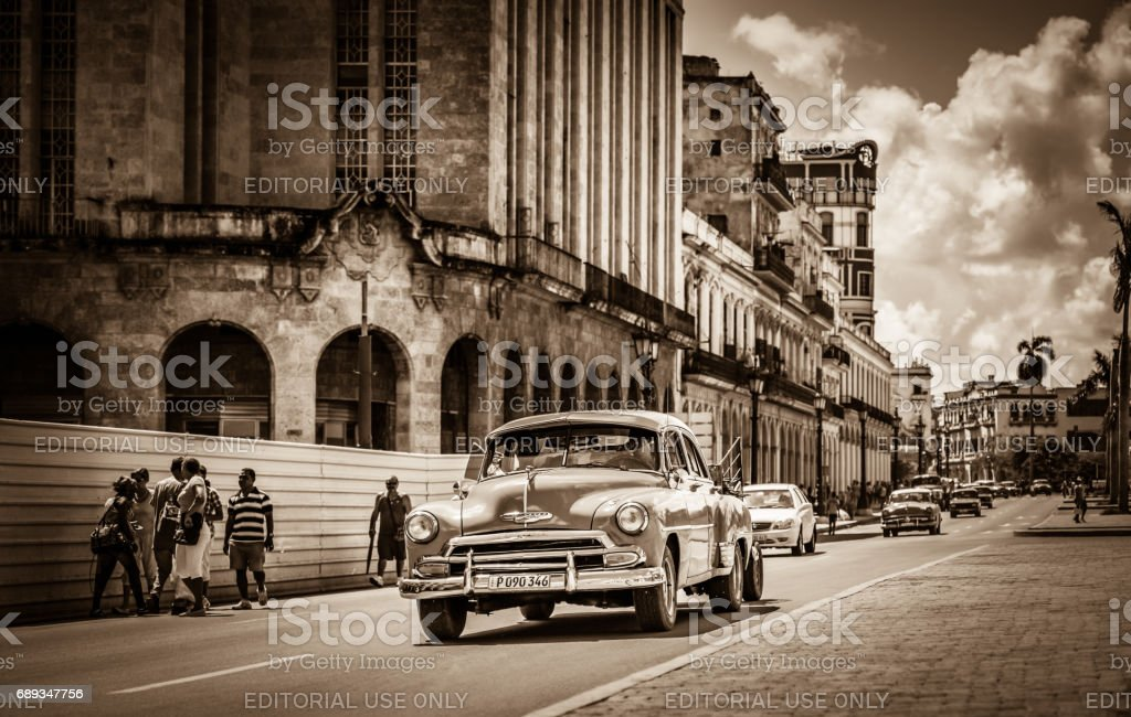 American classic car drives on the main street with street life view...