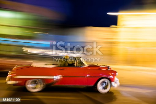 Red, vintage, convertible American car driving down the street at night, blurred motion, Havana, Cuba.