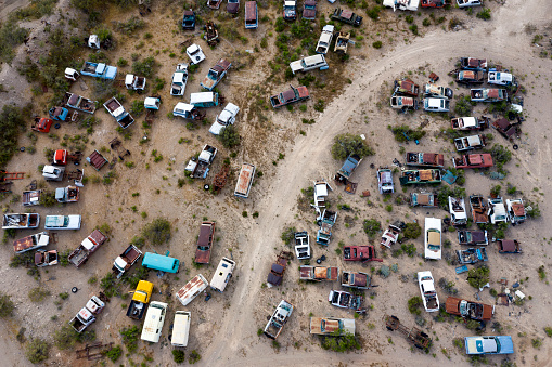 Wrecked, legendary, American classic cars on a junkyard, aerial view, Arizona, USA.