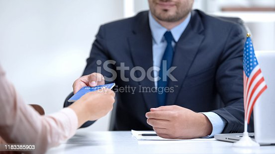 istock American consular officer giving passport to female immigrant, refugee visa 1183385903