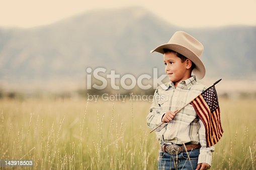 A young cowboy of Hispanic descent shows his colors on the Fourth of July.