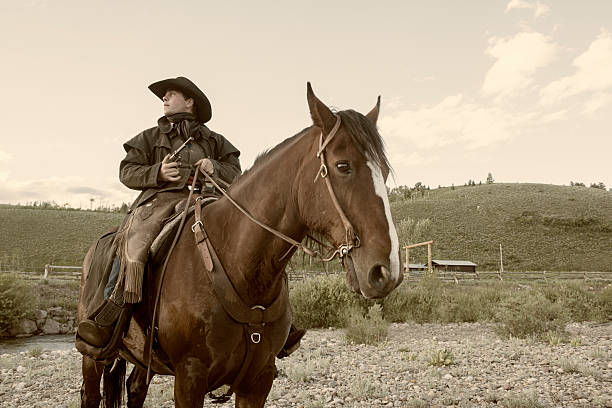 American Cowboy with Gun Wild West Outlaw on Horse This is a horizontal, sepia toned photograph of an outlaw sitting on top of a horse with a pistol drawn. bandit stock pictures, royalty-free photos & images