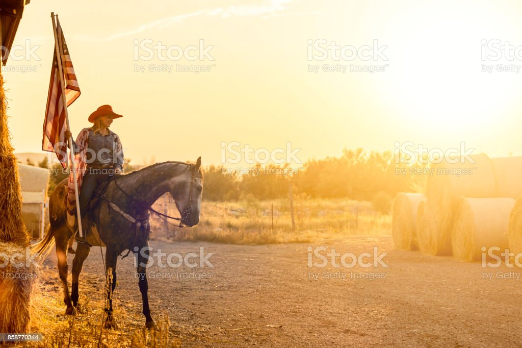American Cowgirl Horseback with American Flag stock photo