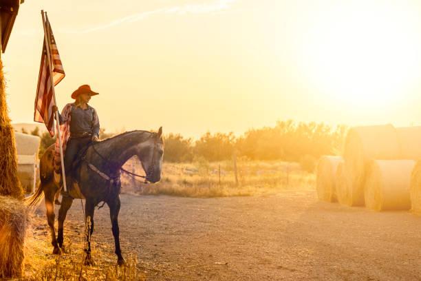 American Cowgirl Horseback with American Flag stock photo