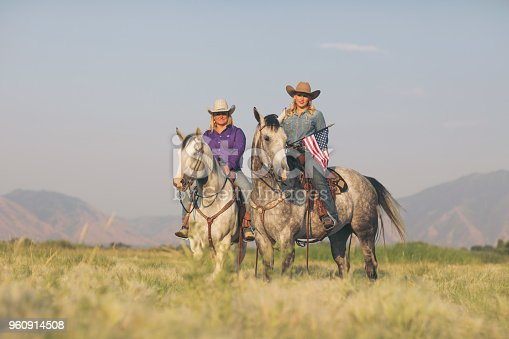 Two American cowgirls on horseback at the ranch are smiling at the camera.  One woman is holding an American flag for the Fourth of July. July has the best summer weather for riding horses at sunset. This photo was taken in Utah, USA.