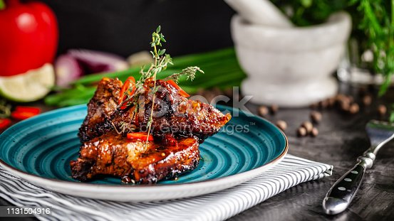 istock American cuisine. Grilled marinated pork ribs on a blue plate with shrimp and spicy chili in barbecue sauce. Background image. copy space 1131504916