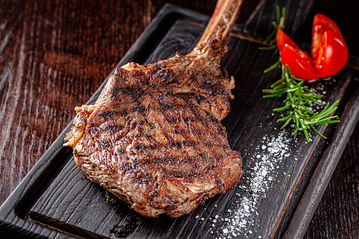 istock American cuisine. Large juicy grilled steak on a tomahawk bone. Beef steak on a wooden board with rosemary and salt. background image, copy space text 1214922916